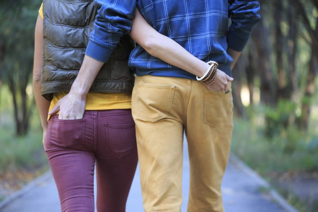 Man and woman are walking down the alley in the park, cuddling, holding hands in the pockets