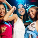 Group of fashionable girls dancing energetically in night club